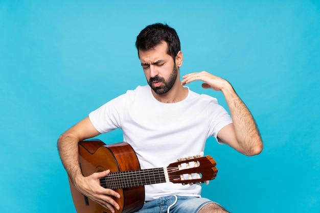 Jovem com guitarra sobre azul isolado com expressão cansada e doente