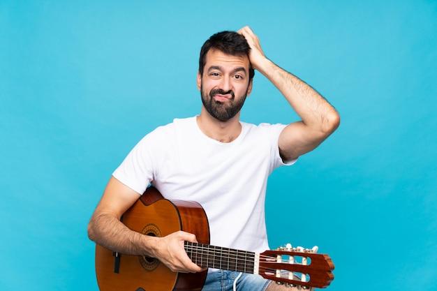 Jovem com guitarra sobre azul isolado com uma expressão de frustração e não compreensão
