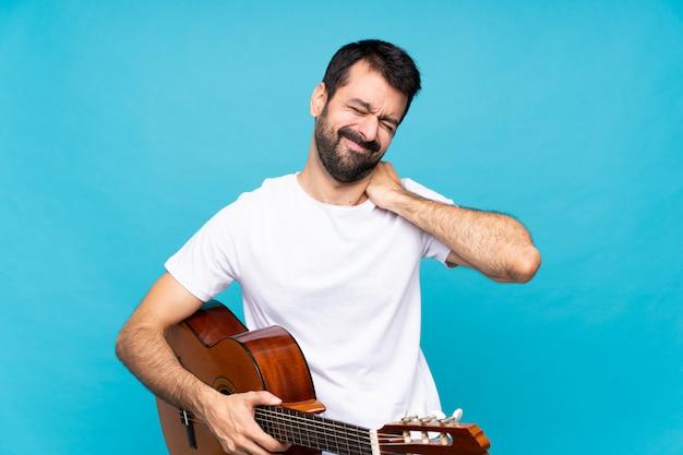 Jovem com guitarra sobre azul, sofrendo de dor no ombro por ter feito um esforço