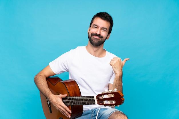 Jovem com guitarra sobre fundo azul isolado com polegares para cima gesto e sorrindo
