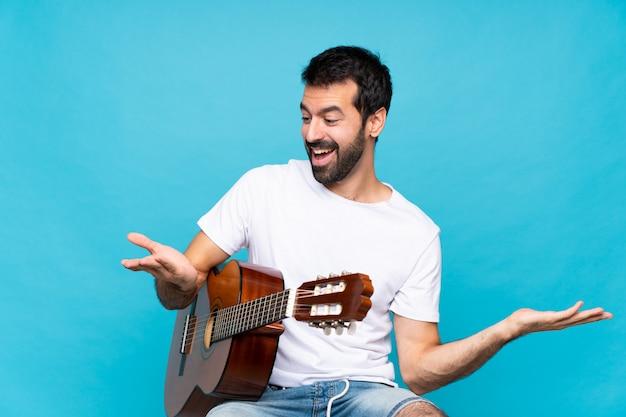 Jovem com guitarra sobre isolado azul segurando copyspace com as duas mãos