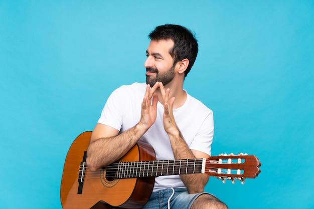 Jovem com guitarra sobre isolado planejando algo
