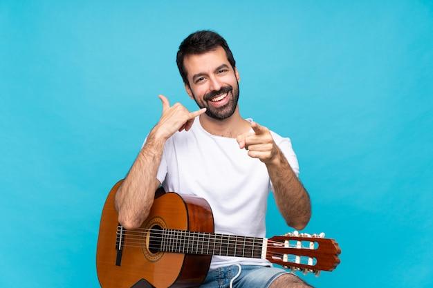 Jovem com guitarra sobre parede azul isolada, fazendo gesto de telefone e apontando a frente