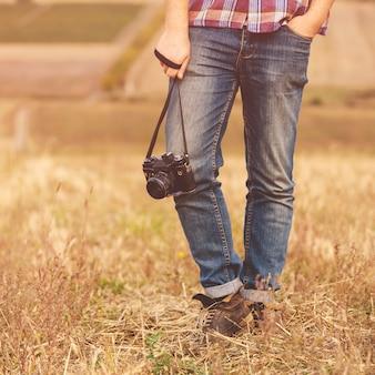 Jovem com hipster de câmera fotográfica retrô ao ar livre