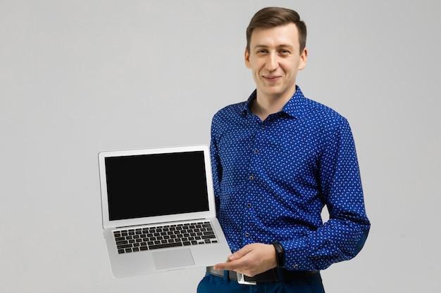 Jovem com laptop com uma tela vazia nas mãos é isolado na luz