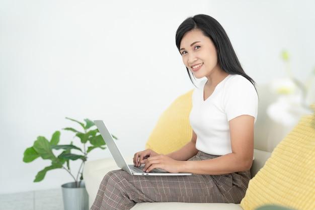 Jovem com laptop moderno, sentado no sofá em casa