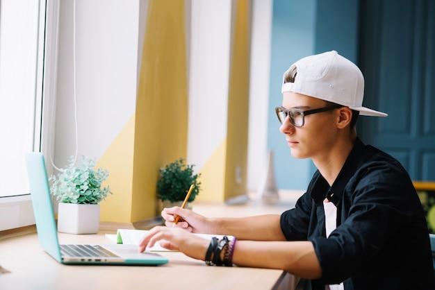 Jovem com laptop na sala de aula