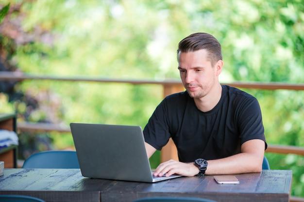 Jovem com laptop no café ao ar livre, bebendo café.