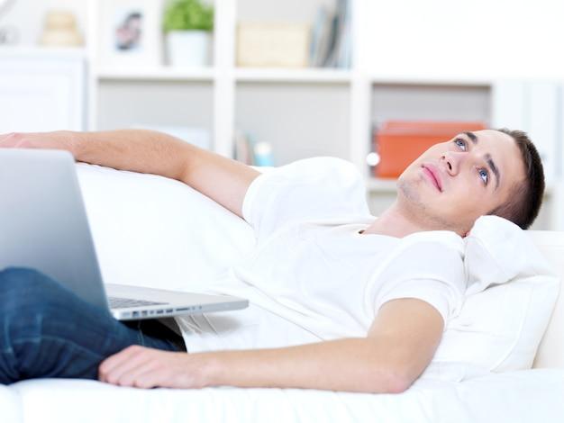 Jovem com laptop olhando para fora no sofá