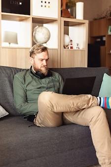 Jovem com laptop sentado no sofá da sala. trabalho em ambiente informal, trabalho remoto, home office, freelancer, auto-isolamento, ideia de procrastinação