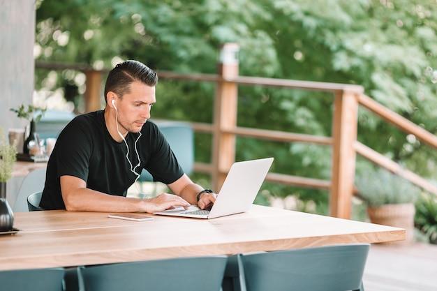 Jovem com laptop trabalha em casa