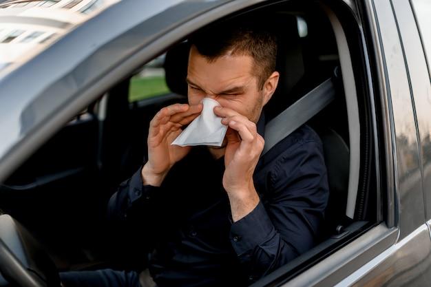 Jovem com lenço. cara doente tem corrimento nasal. modelo masculino faz uma cura para o resfriado comum no carro.