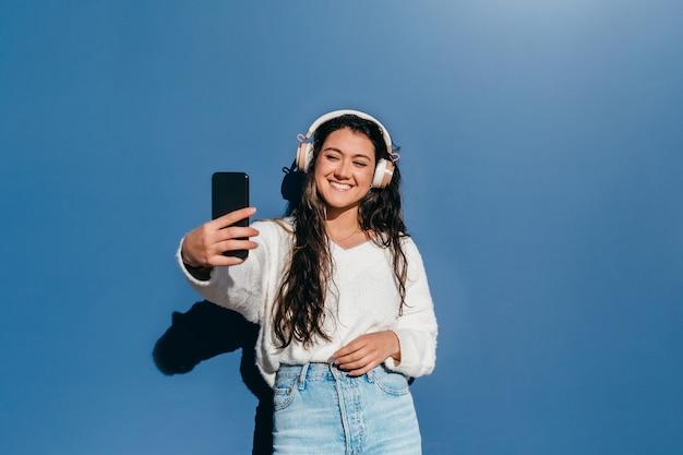 Jovem com longos cabelos castanhos tirando uma selfie com o celular em um fundo azul