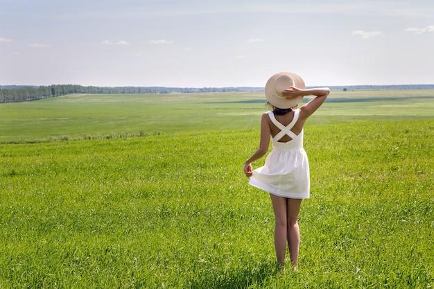 Jovem com longos cabelos escuros em pé em um campo verde