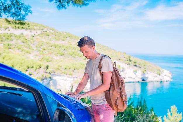 Jovem com mapa viajar de carro nas férias de verão