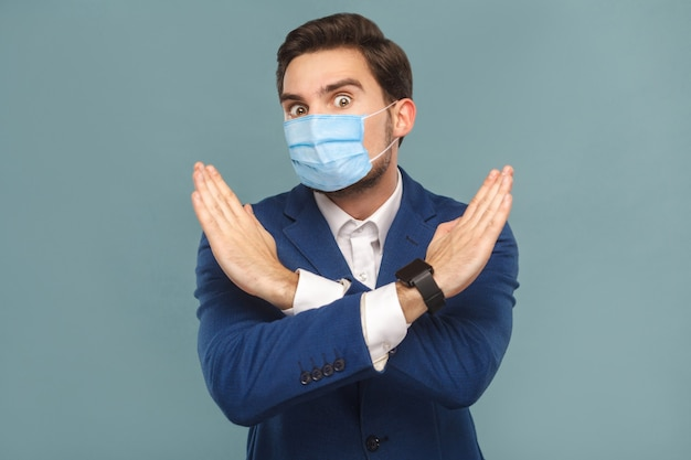 Jovem com máscara cirúrgica médica em pé, mostrando a proibição de mão perto da câmera