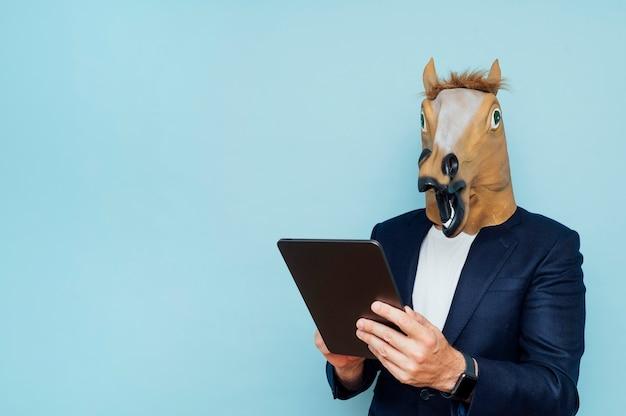 Jovem com máscara de cavalo engraçado funciona com um tablet portátil.