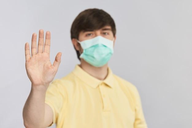 Jovem com máscara de proteção e camisa amarela, mostrando a placa de pare com o braço