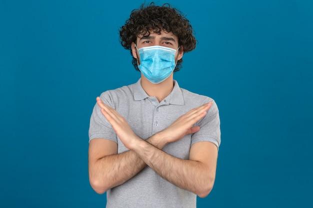 Jovem com máscara de proteção médica em pé com os braços cruzados, fazendo gesto de parada sobre fundo azul isolado