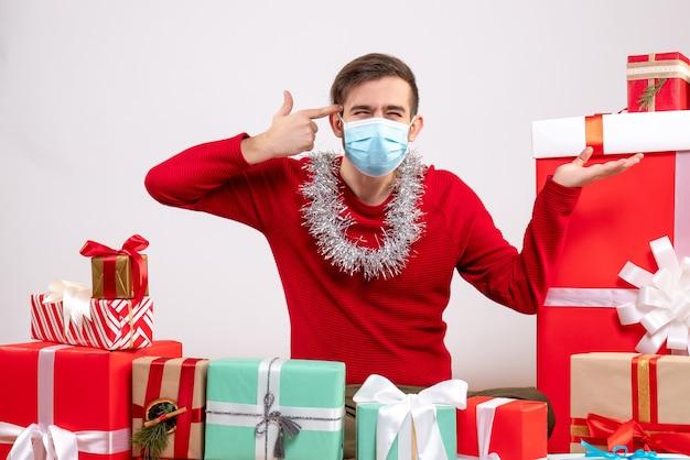 Jovem com máscara e colocando o dedo na têmpora sentado em volta de presentes de natal