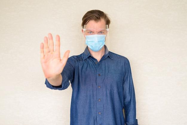 Jovem com máscara e protetor facial mostrando gesto de parada na parede de concreto