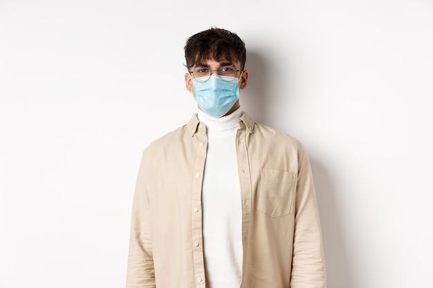 Jovem com máscara facial de covid-19, parecendo alegre, de pé na parede branca. coronavírus, quarentena e conceito de distanciamento social.