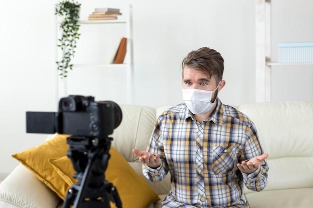 Jovem com máscara facial gravando vídeo em casa