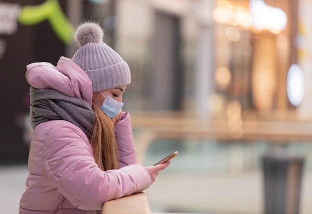 Jovem com máscara facial usando telefone celular no shopping da cidade