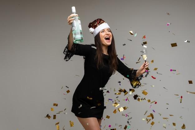 Jovem com máscara festiva com presente e garrafa de vinho, comemorando o feriado em fundo cinza com confete, copie o espaço