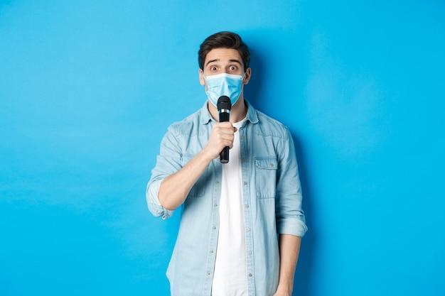 Jovem com máscara médica dando um discurso, segurando o microfone e parecendo confuso, em pé sobre um fundo azul.