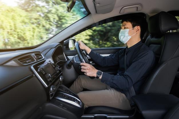 Jovem com máscara médica, dirigindo um carro. para proteger a pandemia de covid-19 (coronavírus)