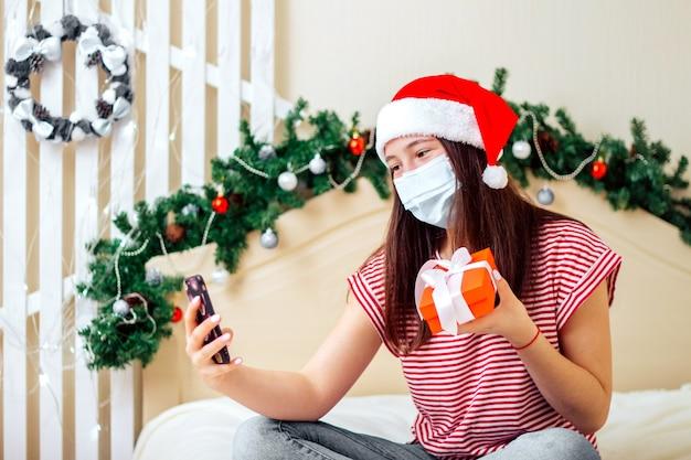 Jovem com máscara médica e caixa de presente sentada na cama com chapéu de papai noel, falando no smartphone