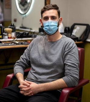 Jovem com máscara médica esperando na barbearia