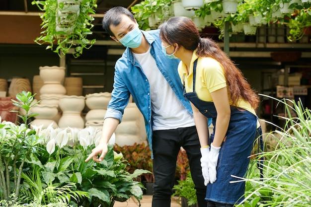 Jovem com máscara médica pedindo ajuda ao trabalhador do centro de jardinagem para escolher plantas e flores