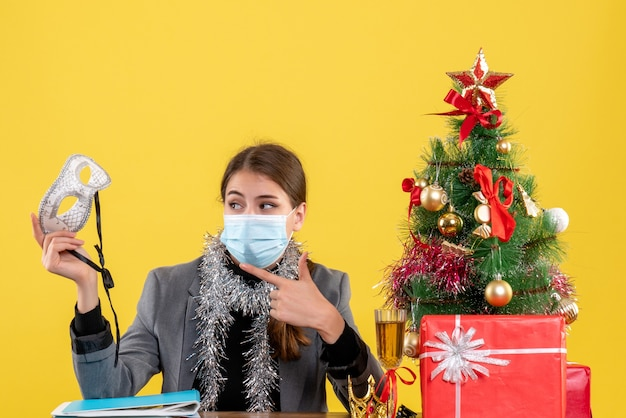 Jovem com máscara médica sentada à mesa mostrando máscara de baile de máscaras com árvore de natal e coquetel de presentes