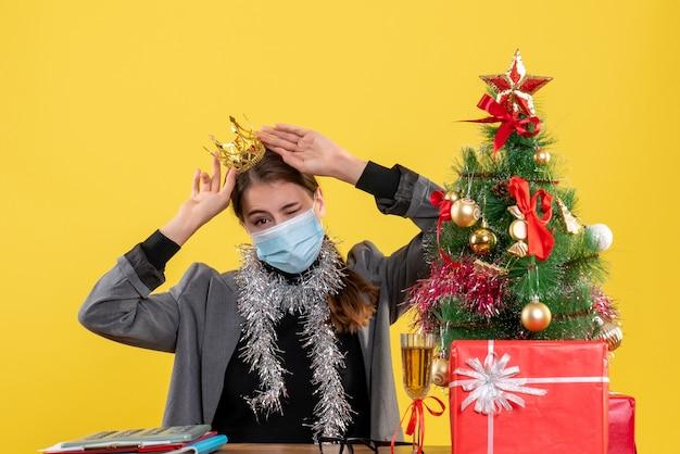 Jovem com máscara médica usando coroa de árvore de natal e coquetel de presentes de frente