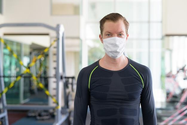 Jovem com máscara para proteção contra surto de coronavírus na academia durante o coronavírus covid-19