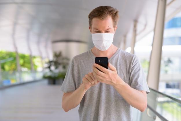 Jovem com máscara para proteção contra surto de vírus corona usando telefone na cidade ao ar livre