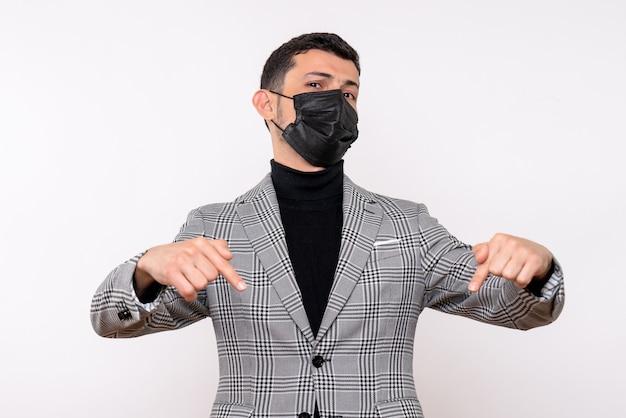 Jovem com máscara preta apontando para o pé no chão em fundo branco isolado