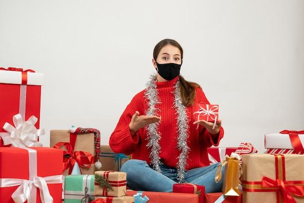 Jovem com máscara preta apontando para seu presente sentada em volta de presentes em branco