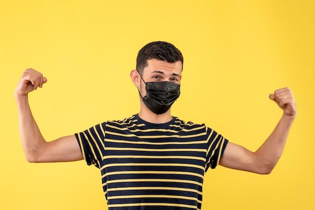 Jovem com máscara preta mostrando fundo amarelo dos músculos do braço