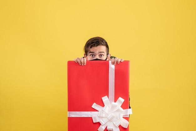 Jovem com máscara preta se escondendo atrás de uma grande caixa de presente amarela