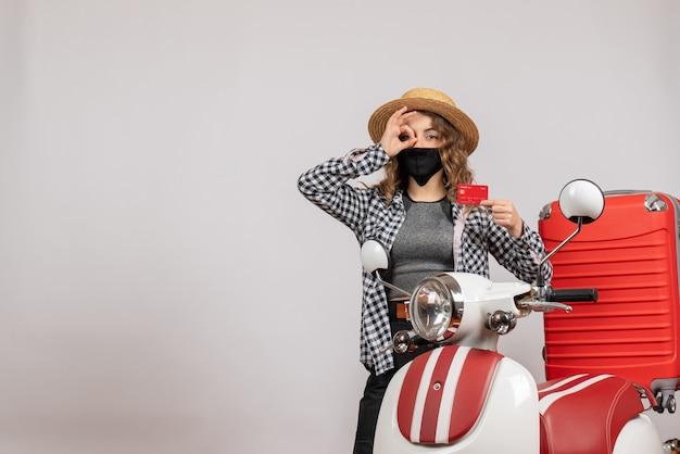 Jovem com máscara preta segurando um cartão e fazendo binóculos com as mãos em pé perto da motocicleta vermelha