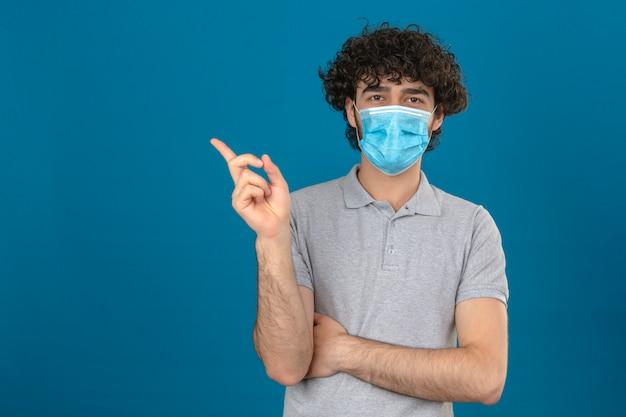 Jovem com máscara protetora médica apontando para o lado, olhando para a câmera sobre fundo azul isolado