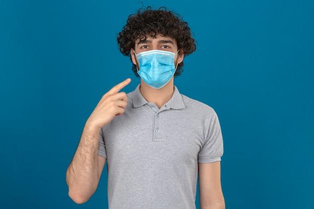 Jovem com máscara protetora médica apontando para sua máscara, olhando para a câmera com cara séria sobre fundo azul isolado