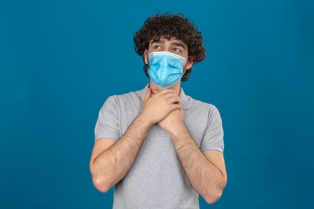 Jovem com máscara protetora médica mantém as mãos no pescoço por causa de uma dor de garganta sobre um fundo azul isolado