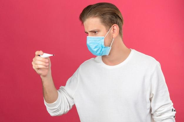 Jovem com máscara protetora médica olhando para o termômetro digital em pânico chocado e surpreso com o fundo rosa isolado