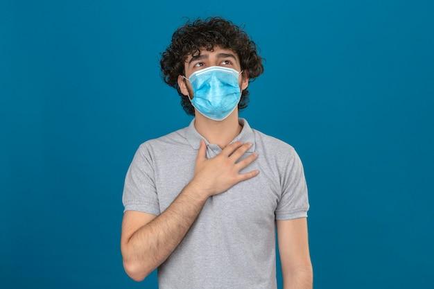 Jovem com máscara protetora médica tocando no peito para verificar o pulmão enquanto respira sobre fundo azul isolado