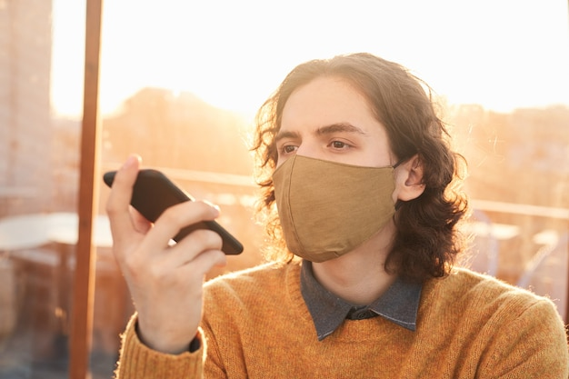 Jovem com máscara protetora ouvindo mensagem de áudio em seu telefone celular