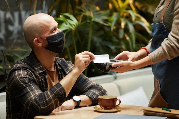 Jovem com máscara protetora, pagando seu pedido com cartão de crédito, sentado em um café